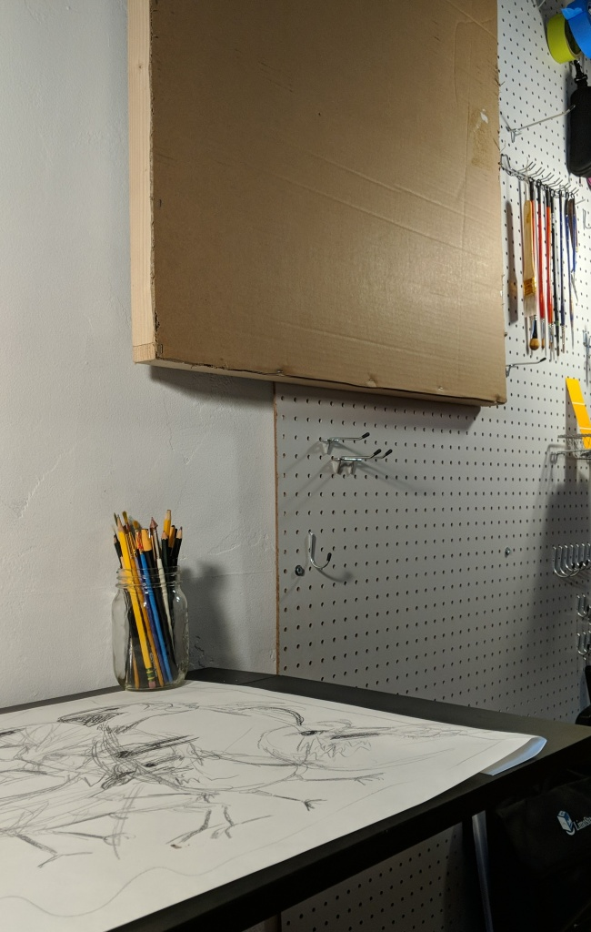 Interior close-up photo of a studio space, showing peg-board wall with hanging paint brushes and a blank art board made with a wooden frame covered in cardboard. Beside this is a small black desk with a large sketch of several birds.